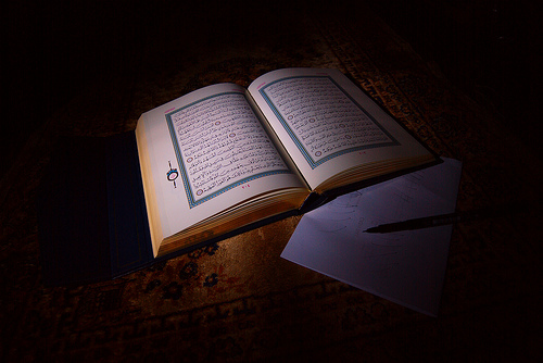Qur'an open with pen and paper next to it